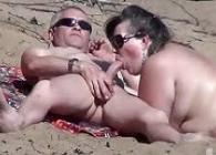 Madura viciosa hace una mamada a su esposo en una playa nudista